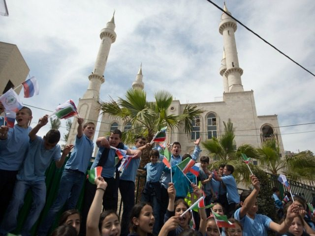 Residents of the Arab Israeli town of Abu Ghosh wave the Chechen flag during the dedication ceremony the new Akhmad Kadyrov mosque, on March 23 2014.