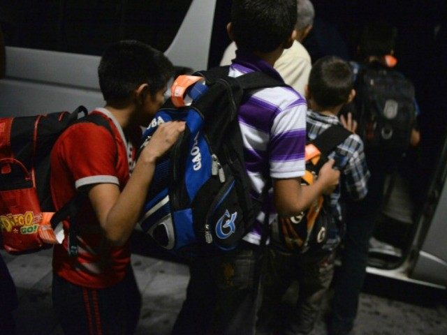 Guatemalan children caught in Mexico while trying to migrate illegally into the United States, queue before climbing into a minibus at Aurora international airport in Guatemala City on July 14, 2014 upon their arrival after being deported from Mexico. US authorities have detained some 57,000 unaccompanied minors since October, twice …