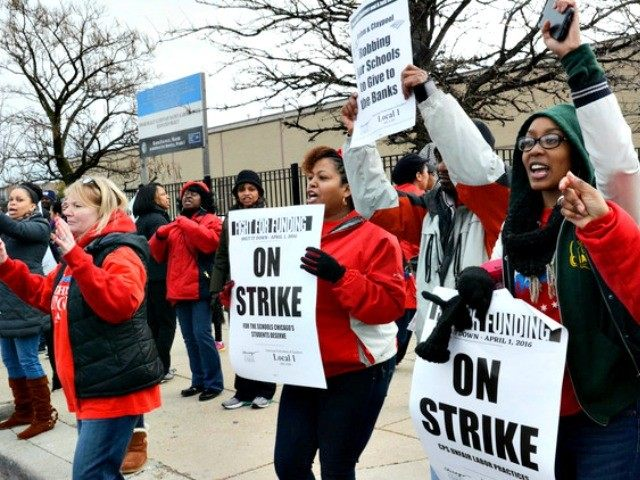 Chicago teachers and supporters carry picket signs outside Beasley Academic Center in Chicago, Friday, April 1, 2016, during a one-day strike they say is aimed at getting lawmakers to adequately fund education and other programs in the nation's third-largest district. (Brian Jackson/Chicago Sun-Times via AP)MANDATORY CREDIT, MAGS OUT, NO SALES; …