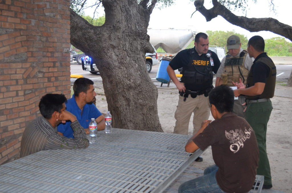 Brooks County volunteer deputies provide water to two Honduran men and a Guatemalan who had been wandering for three days without food and water. (File Photo: Breitbart Texas/Bob Price)