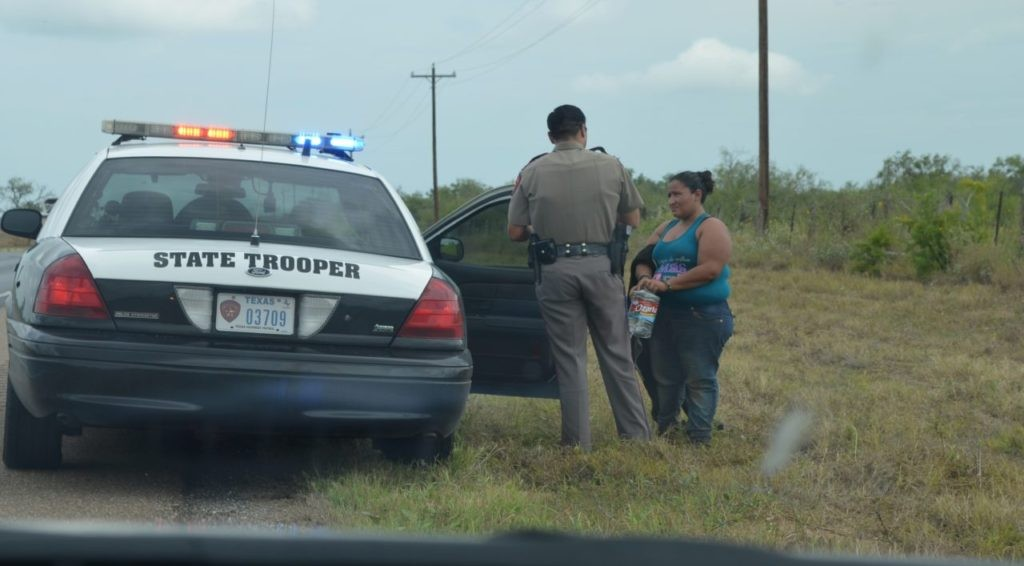 Texas DPS Trooper assists an illegal immigrant who had been left behind without water after falling behind her group. (File Photo: Breirbart Texas/Bob Price)
