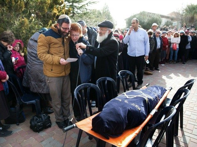 Natan, the husband of Dafna Meir and her son speak during her funeral ceremony in the Jewish settlement of Otniel near the flashpoint city of Hebron in the southern West Bank on January 18, 2016.