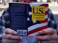 A man holding a copy of the U.S. Constitution on May 1, 2014 in New York City.