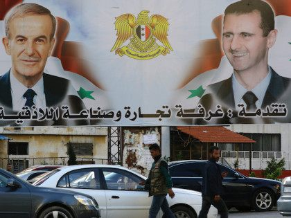 A billboard sponsored by Latakia's chamber of commerce and industry shows pictures of Syrian President Bashar al-Assad (R) and his late father former president Hafez al-Assad in the coastal city of Latakia, the provincial capital of the heartland of Syrian president's Alawite sect, on March 17, 2016. / AFP / …