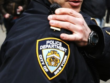 An NYPD officer talks on his radio while people take part in a protest against Republican presidential candidate Donald Trump, on March 19, 2016 in New York City.