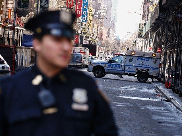 NYPD officers stand guard in Times Square after it was evacuated after a suspicious package call in New York on March 28, 2016. Investigators from the NYPD determined that the item was in fact a piece of garbage. / AFP / KENA BETANCUR (Photo credit should read KENA BETANCUR/AFP/Getty Images)