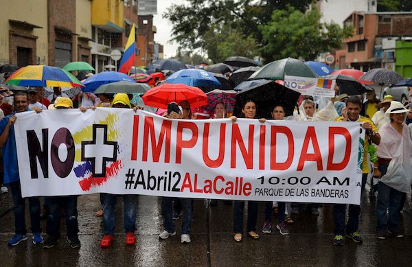 "People hold a banner reading ""No More impunity"" as they they take part in the ""No More"" march against the government of President Juan Manuel Santos and the Revolutionary Armed Forces of Colombia (FARC) guerrillas in Cali, department of Valle del Cauca, Colombia, on April 2, 2016. The government of President Santos and the FARC have been holding peace talks for three years to end a half-century guerrilla war that has killed more than 260,000 people. AFP PHOTO / LUIS ROBAYO / AFP / LUIS ROBAYO (Photo credit should read LUIS ROBAYO/AFP/Getty Images)"