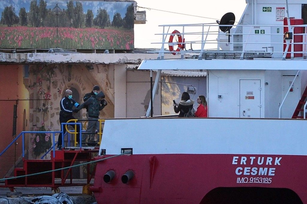 """A migrant is escorted by Frontex officials as he embarks on a Turkish catamaran to be sent back to Turkey early on April 4, 2016 at the port of Chios. Greece sent a first wave of migrants back to Turkey on April 4 under an EU deal that has faced heavy criticism from rights groups. Under the agreement, designed to halt the main influx which comes from Turkey, all """"irregular migrants"""" arriving since March 20 face being sent back, although the deal calls for each case to be examined individually. For every Syrian refugee returned, another Syrian refugee will be resettled from Turkey to the EU, with numbers capped at 72,000. / AFP / LOUISA GOULIAMAKI (Photo credit should read LOUISA GOULIAMAKI/AFP/Getty Images)"""