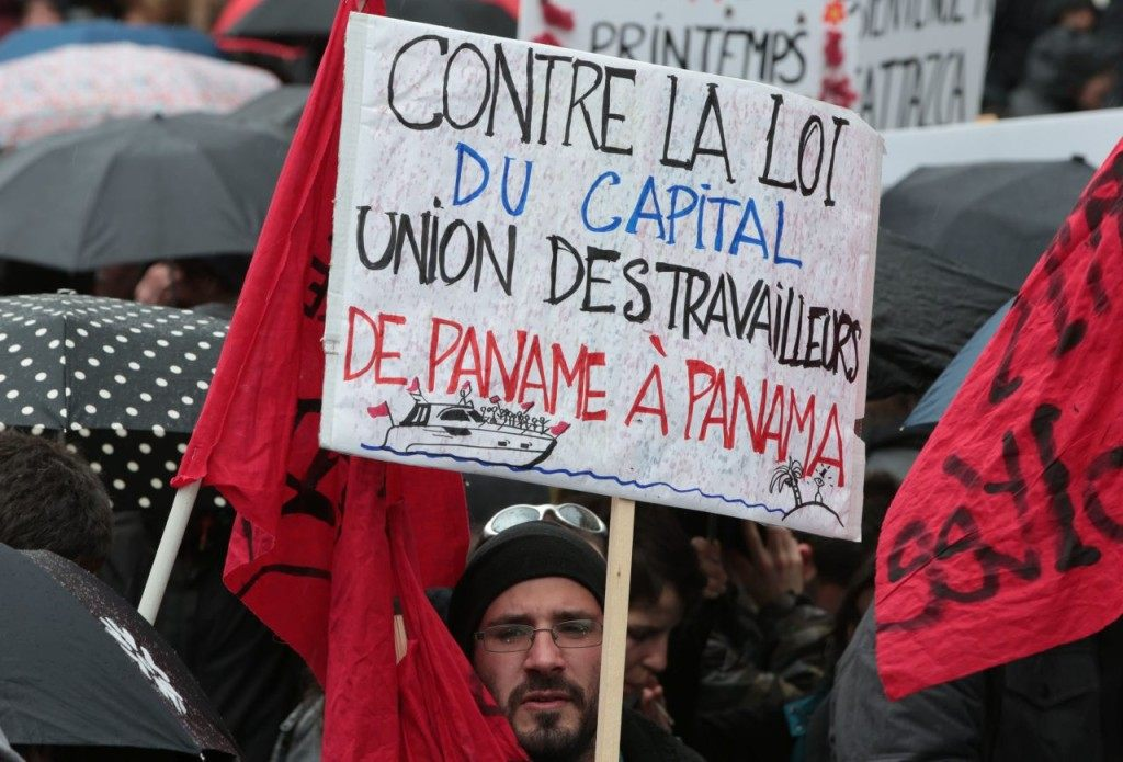 "A man holds a placard reading ""Against the law of the capital, Union of workers from Paname (Paris) to Panama"" (JOEL SAGET/AFP/Getty Images)"