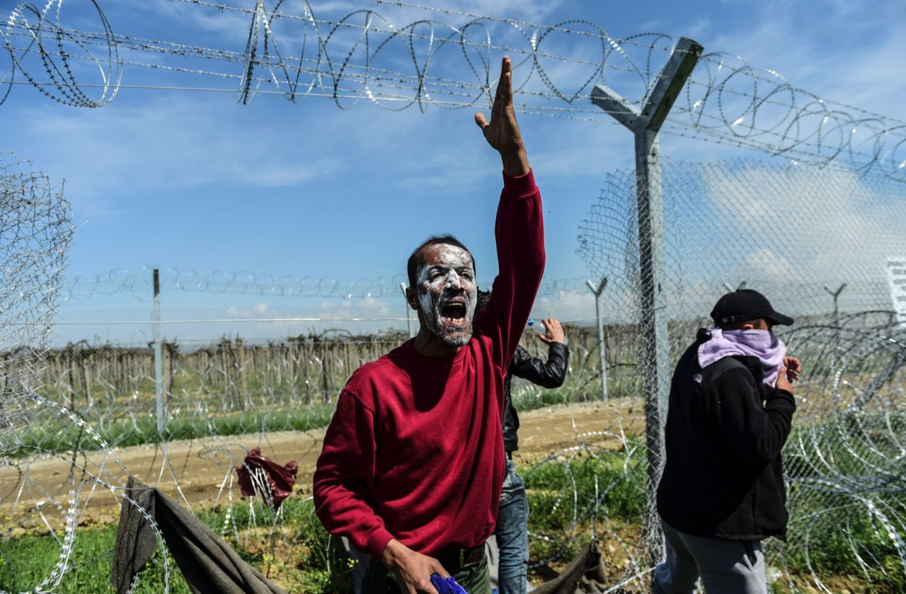 TOPSHOT - A man calls to other refugees and migrants to walk through the torn down wire fencing along the border into Macedonia during clashes with Macedonian security as they protest to reopen the border near their makeshift camp in the northern Greek border village of Idomeni, on April 10, 2016. Dozens of people were hurt when police fired tear gas on a group of migrants as they tried to break through a fence on the Greece-Macedonia border, the medical charity Doctors without Borders (MSF) said. Efforts by the Greek authorities to persuade migrants to leave Idomeni and move to nearby reception centres have not been successful, with many people preferring to stay put in the hope the border will be opened, despite the controversial EU-Turkey deal to stem the flow of refugees that took effect three weeks ago. / AFP / BULENT KILIC (Photo credit should read BULENT KILIC/AFP/Getty Images)