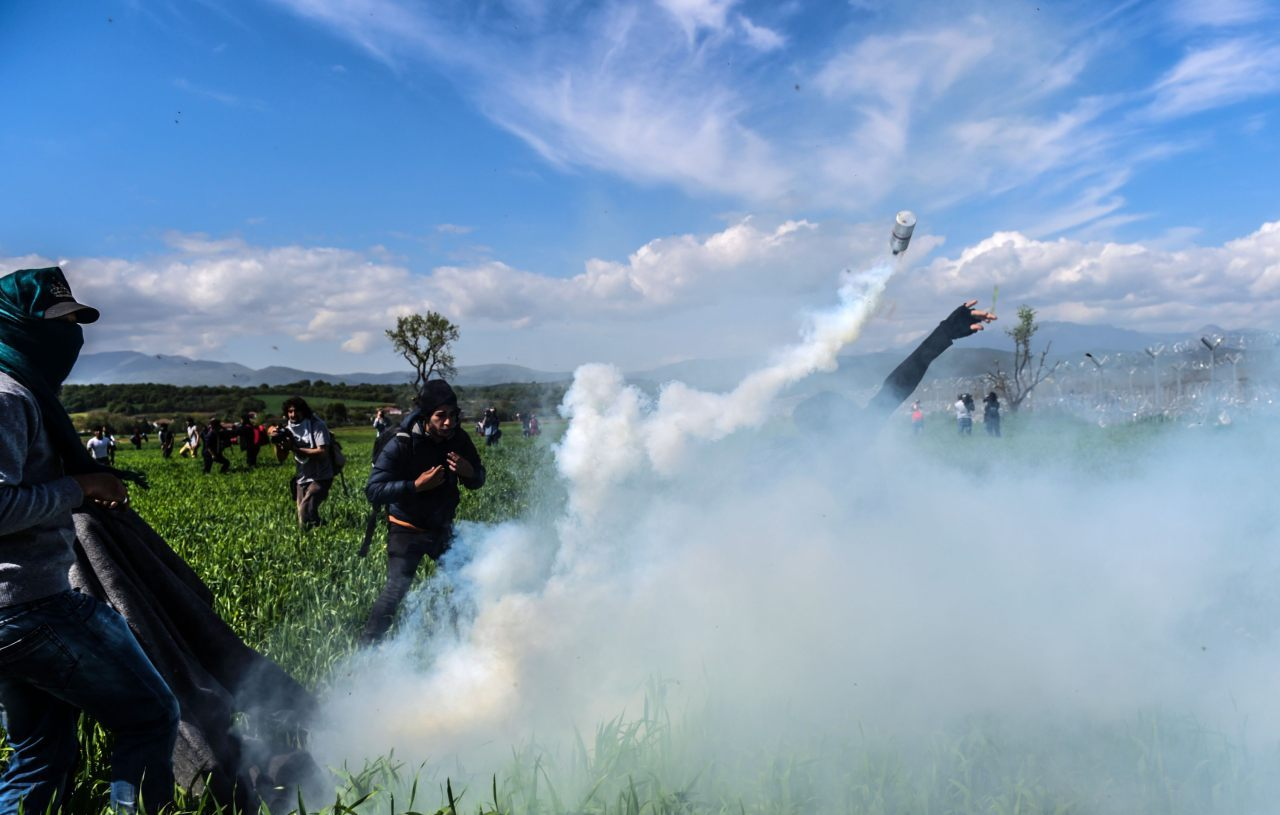 Migrants showered with tear gas (BULENT KILIC/AFP/Getty Images)