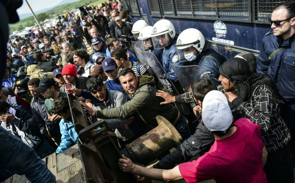 TOPSHOT - Refugees and migrants pull a wagon in an attempt to go through a barricade held by Greek police as they protest to call for the reopening of the border near their makeshift camp in the northern border village of Idomeni, on April 11, 2016. A plan to send back migrants from Greece to Turkey sparked demonstrations by local residents in both countries days before the deal brokered by the European Union is set to be implemented. / AFP / BULENT KILIC (Photo credit should read BULENT KILIC/AFP/Getty Images)