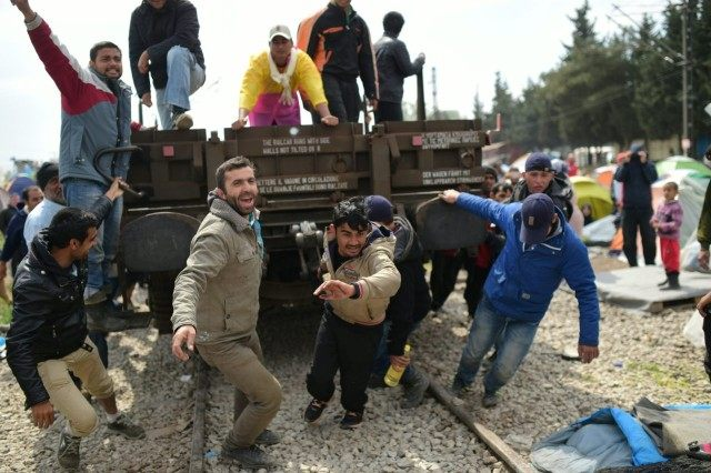 TOPSHOT - Refugees and migrants pull a wagon in an attempt to go through a barricade held by Greek police as they protest to call for the reopening of the border near their makeshift camp in the northern border village of Idomeni, on April 11, 2016. A plan to send …
