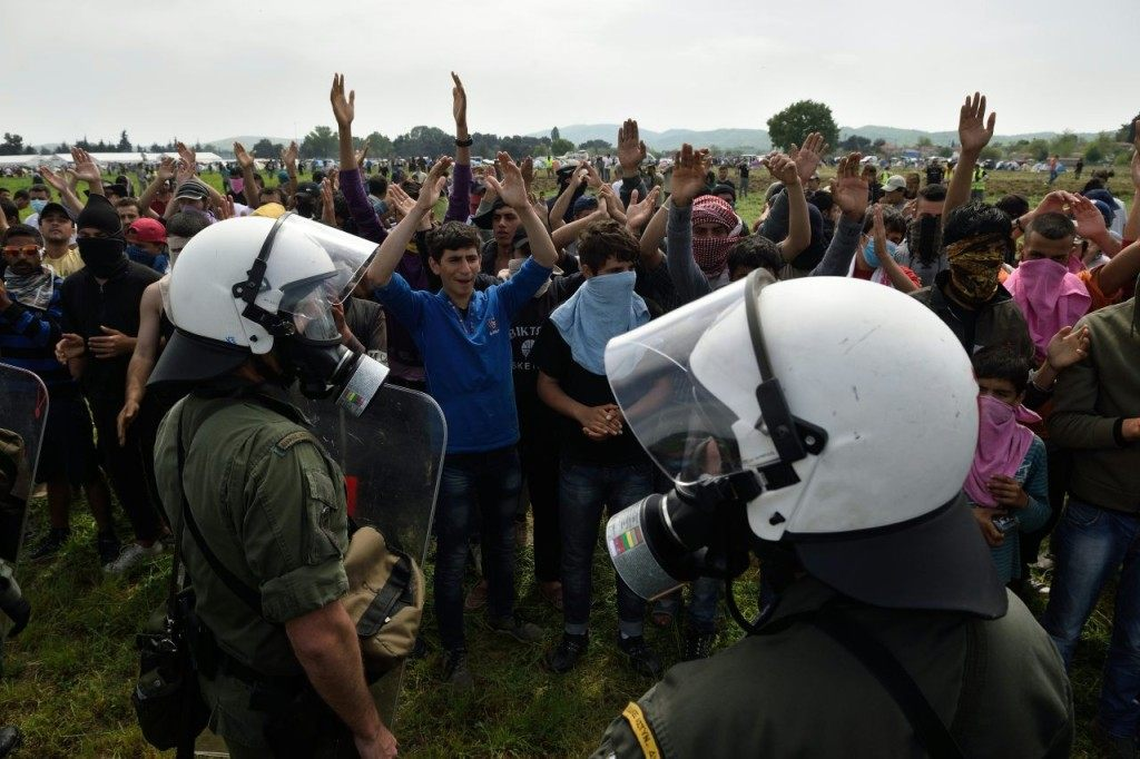 TOPSHOT - Migrants and refugees hold a protest to call for the reopening of the border near their makeshift camp at the Greek-Macedonian border in Idomeni, on April 13, 2016. About 100 migrants spread out over about 100 metres (yards) tugging at the wire fence, but swiftly pulled back when two squads of Greek riot police moved in, the reporter said. The Greek riot police positioned themselves between the migrants and the Macedonian fence, ending the incident. / AFP / DANIEL MIHAILESCU (Photo credit should read DANIEL MIHAILESCU/AFP/Getty Images)