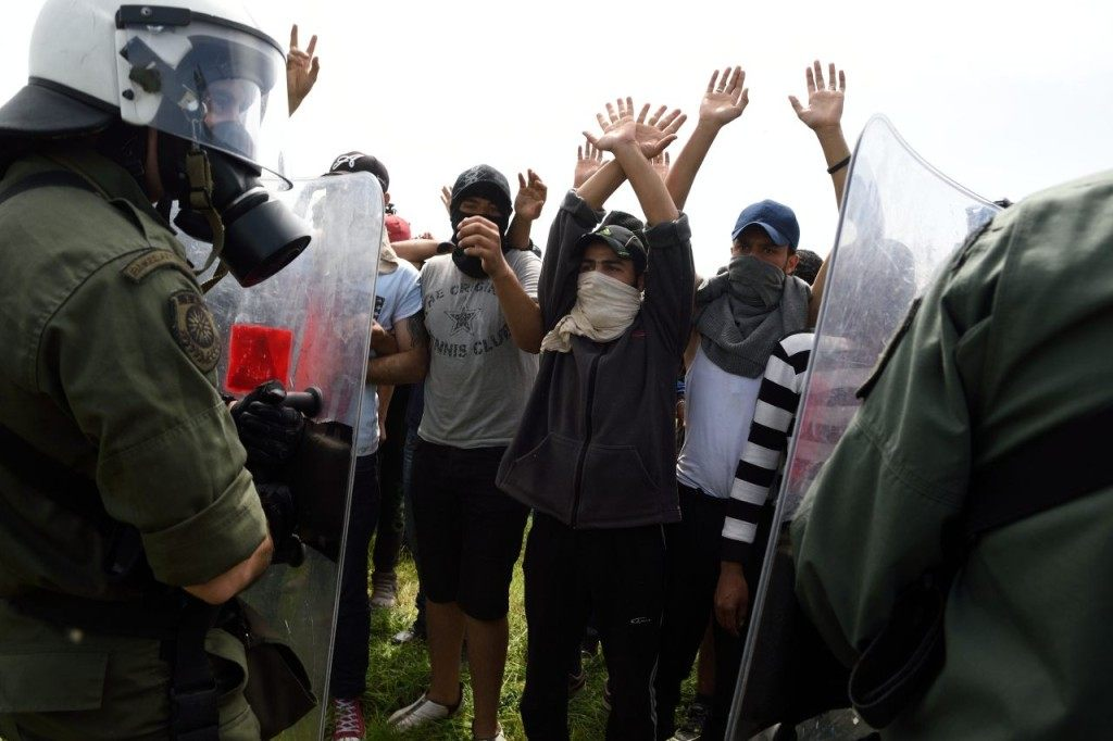 Men with their mouths covered raise their hands as migrants and refugees protest in the front of Greek police forces as around one hundred of them try to break down the border fence between Greece and Macedonia at the makeshift camp near the Greek village of Idomeni on April 13, 2016. Macedonia police on April 13 fired tear gas and stun grenades at migrants staging a protest at the country's border fence with Greece, an AFP reporter said. About 100 migrants spread out over about 100 metres (yards) tugging at the wire fence, but swiftly pulled back when two squads of Greek riot police moved in, the reporter said. / AFP / DANIEL MIHAILESCU (Photo credit should read DANIEL MIHAILESCU/AFP/Getty Images)