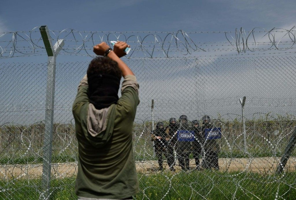 TOPSHOT - A man looks at Macedonia police through a fence as migrants and refugees hold a protest to call for the reopening of the border near their makeshift camp at the Greek-Macedonian border in Idomeni, on April 13, 2016. About 100 migrants spread out over about 100 metres (yards) tugging at the wire fence, but swiftly pulled back when two squads of Greek riot police moved in, the reporter said. The Greek riot police positioned themselves between the migrants and the Macedonian fence, ending the incident. / AFP / DANIEL MIHAILESCU (Photo credit should read DANIEL MIHAILESCU/AFP/Getty Images)