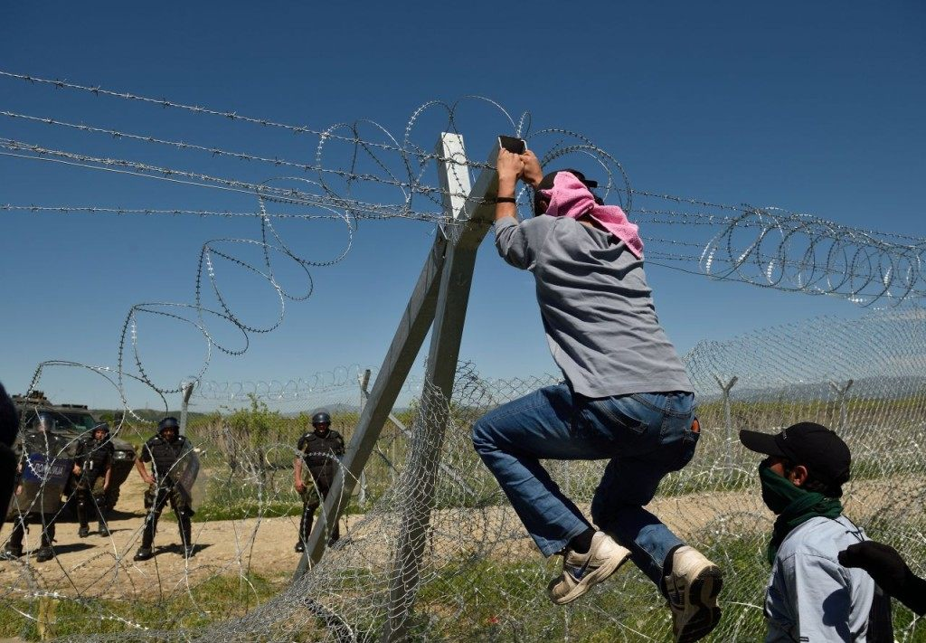 "Refugees and migrants try to break down the border fence between Greece and Macedonia at the makeshift camp near the village of Idomeni, on April 16, 2016. According to statistics released on on April 8 by the International Organization of Migrants (IOM), more than 152,000 people have arrived in Greece by sea from Turkey since January 1, nearly three-quarters of whom were Syrians. Greek Prime Minister Alexis Tsipras accused neighbouring Macedonia on April 11, 2016 of ""shaming"" Europe by firing tear gas and rubber bullets at migrants desperately trying to break through a border fence. Tensions are still running high after April 10's violence, which saw 250 refugees and migrants hurt at the flashpoint Idomeni crossing as they tried to force their way into Macedonia. / AFP / DANIEL MIHAILESCU (Photo credit should read DANIEL MIHAILESCU/AFP/Getty Images)"
