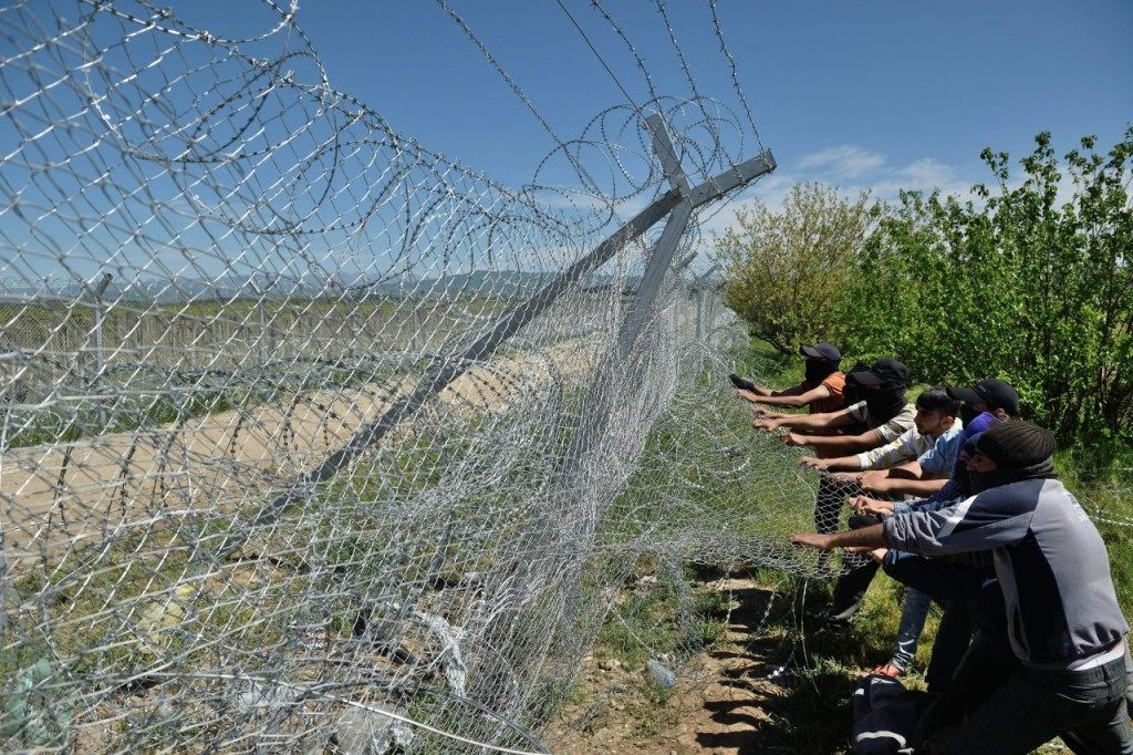 "Refugees and migrants try to break down the border fence between Greece and Macedonia near the makeshift camp at the Greek-Macedonian border near the village of Idomeni, on April 16, 2016. According to statistics released on on April 8 by the International Organization of Migrants (IOM), more than 152,000 people have arrived in Greece by sea from Turkey since January 1, nearly three-quarters of whom were Syrians. Greek Prime Minister Alexis Tsipras accused neighbouring Macedonia on April 11, 2016 of ""shaming"" Europe by firing tear gas and rubber bullets at migrants desperately trying to break through a border fence. Tensions are still running high after April 10's violence, which saw 250 refugees and migrants hurt at the flashpoint Idomeni crossing as they tried to force their way into Macedonia. / AFP / DANIEL MIHAILESCU (Photo credit should read DANIEL MIHAILESCU/AFP/Getty Images)"