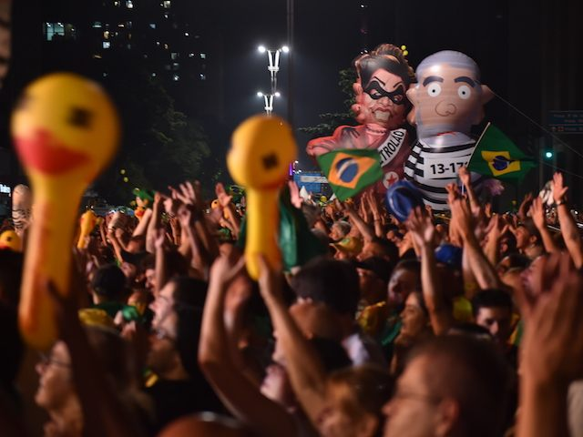 TOPSHOT - Supporters of the impeachment of Brazilian President Dilma Rousseff follow on big screens as lawmakers vote on whether the impeachment of Rousseff will move forward, in Sao Paulo, Brazil, on April 17, 2016. The voting followed a raucous debate that transfixed the deeply divided nation. The opposition needs a total of 342 out of the 513 deputies in the lower house of Congress to authorize the trial. Rousseff, whose approval rating has plunged to a dismal 10 percent, faces charges of embellishing public accounts to mask the budget deficit during her 2014 reelection. / AFP / NELSON ALMEIDA (Photo credit should read NELSON ALMEIDA/AFP/Getty Images)