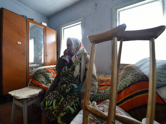 "Maria Urupa sits on a bed in her house in Paroshev village, Chernobyl region on April 8, 2016. Maria Urupa, who is in her early 80s, also calls the exclusion zone home but is less enthusiastic about her living environment. Like most of the ""samosely"", or self-returners as inhabitants of the exclusion zone are known, she lives in a dilapidated wooden house in spartan conditions. / AFP / SERGEI SUPINSKY (Photo credit should read SERGEI SUPINSKY/AFP/Getty Images)"