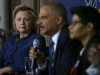 Democratic presidential candidate former Secretary of State Hillary Clinton (L) looks on as former attorney general Eric Holder speaks April 20, 2016 in Philadelphia.