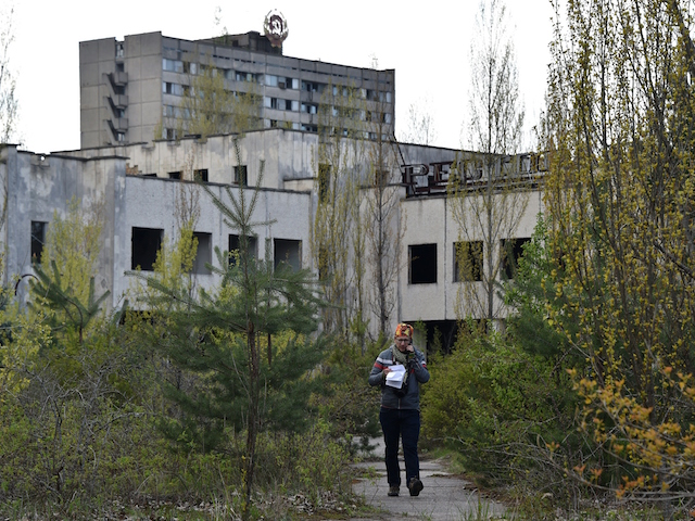 "A man walks through the ""ghost town"" of Pripyat near the Chernobyl Nuclear Power Plant on April 22, 2016. April 26, 2016 marks the 30th anniversary of the Chernobyl nuclear disaster. / AFP / GENYA SAVILOV (Photo credit should read GENYA SAVILOV/AFP/Getty Images)"