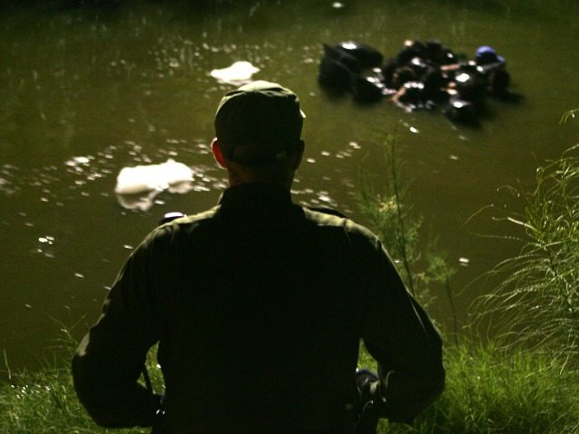 A US Border Patrol agent watches as a group of people use inner tubes to float down the New River, reportedly the most polluted river in the US, after illegally crossing the US/Mexico border on March 27, 2005 near Calexico, California. The black plastic bags are for carrying a dry …