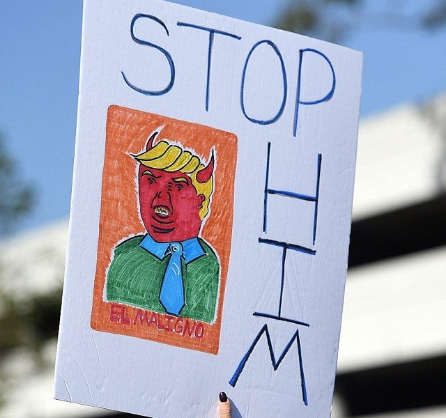 A protester holds up a sign during a rally against US Republican presidential candidate Donald Trump in Burlingame, California on April 29, 2016.  Trump is delivering the keynote address at the California Republican Party's CAGOP 2016 Convention in Burlingame. / AFP / Josh Edelson        (Photo credit should read JOSH EDELSON/AFP/Getty Images)