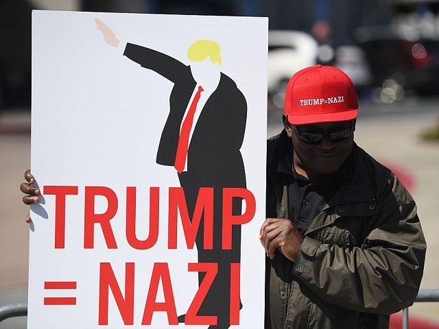 A protester holds up a sign during a protest outside the Hyatt Regency Hotel where republican presidential candidate Donald Trump was speaking in Burlingame, California on April 29, 2016. Hundreds of protesters jostled with police in riot gear outside a California hotel where Republican presidential frontrunner Donald Trump was to …