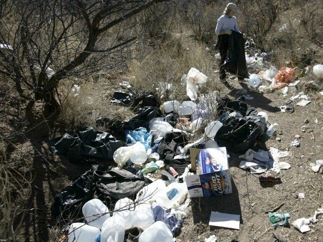 A volunteer picks up trash on a immigrant passage near Arivaca, Arizona. File.