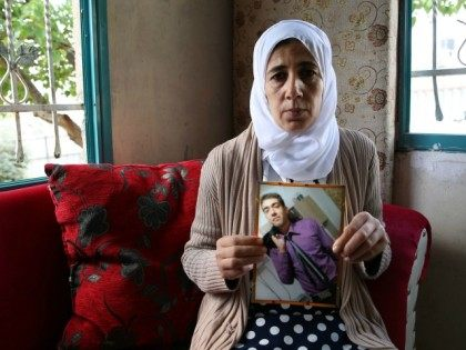 Manal al-Saayed, mother of Hisham, a Bedouin Muslim Arab with Israeli citizenship without any apparent connection to the Israeli authorities who disappeared a year beforehand from his home in the Negev desert in Israel, shows a photo of her son at their family home in the southern Israeli town of …