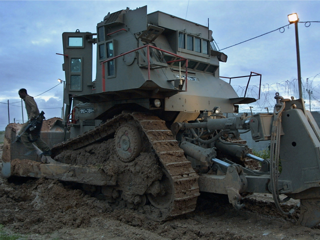 An Israeli soldier climbs down from a bulldozer after returning from the Gaza Strip February 13, 2002 at the Israeli controlled Erez crossing.