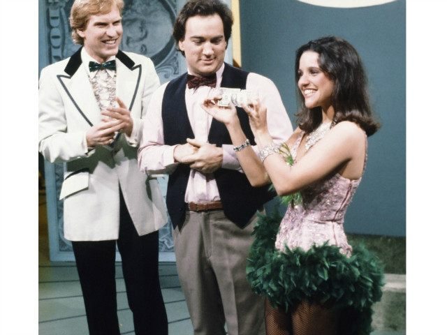SATURDAY NIGHT LIVE -- Episode 4 -- Pictured: (l-r) Brad Hall as Ralph Curtis, Jim Belushi as Dale Butterworth, Julia Louis-Dreyfus as model during 'You Win a Dollar' skit on November 5, 1983 -- Photo by: Alan Singer/NBC/NBCU Photo Bank