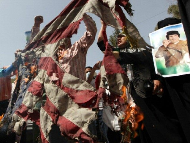 Supporters of Libyan leader Moamer Kadhafi burn a US flag as they protest outside his house which was hit by a NATO air strike overnight in the Gargur area of Tripoli on May 1, 2011 as the Libyan regime said the raid killed Kadhafi's youngest son and three grandchildren but …