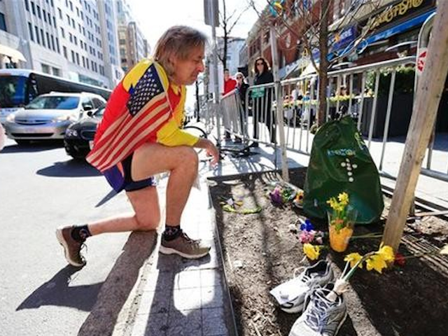 Ron McCracken of Dallas pays his respects at a makeshift memorial honoring to the victims of the 2013 Boston Marathon bombings ahead of Monday's 118th Boston Marathon, Sunday, April 20, 2014, in Boston. (AP Photo/Matt Rourke)