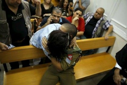 Sgt. Elor Azariais the Israeli soldier, charged with manslaughter by the Israeli military after he shot a wounded Palestinian assailant as he lay on the ground in Hebron on March 24, is hugged by his mother during a hearing at a military court in Jaffa near Tel Aviv, Israel April …
