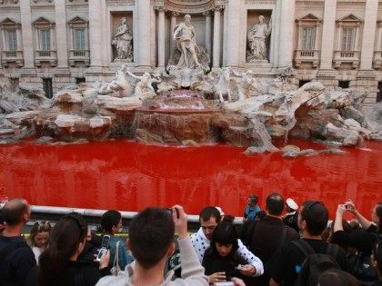 """A red liquid was poured into the Trevi fountain in the center of Rome, 19 October 2007. A substance has colored the water and the gesture was claimed by the artistic group """"Action futurist 2007"""". AFP PHOTO / CHRISTOPHE SIMON (Photo credit should read CHRISTOPHE SIMON/AFP/Getty Images)"""