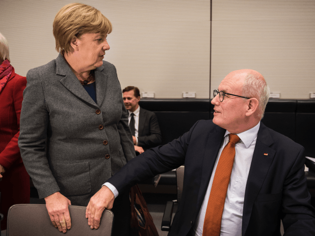 Leader of CDU/CSU parliamentary group Volker Kauder speaks with German Chancellor Angela Merkel at a conservative CDU/CSU parliamentary group meeting at the German lower house of parliament (Bundestag) on November 26, 2015 in Berlin.