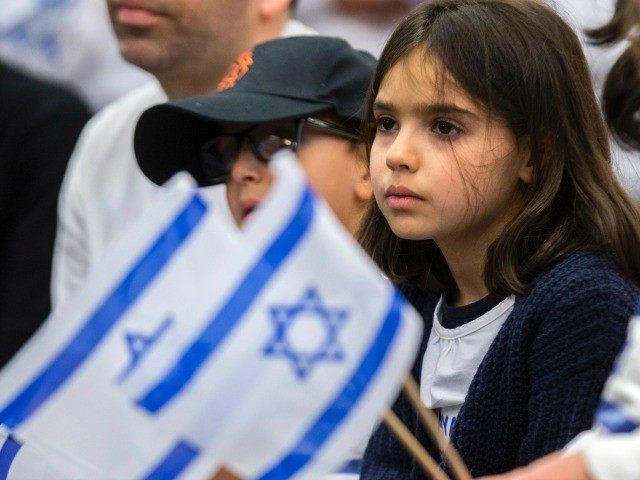 The Jewish new immigrant members of the Ammar family from France, who are making Aliyah (Immigration to Israel), wave Israeli national flags upon their arrival at Ben Gurion International airport on December 8, 2015 in Lod, about 15 kms east of Tel Aviv, during the Jewish holiday of Hanukkah.