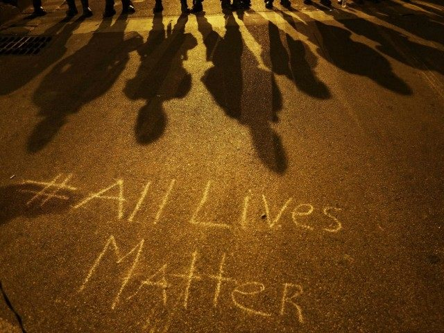 "A message reading ""All Lives Matter"" is written on the pavement as police in riot gear cast shadows while standing in line ahead of a curfew Friday, May 1, 2015, in Baltimore. (AP Photo/David Goldman)"