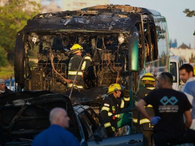 Israeli firemen and emergency services check the remains of a burnt-out bus after extinguishing the flames following an explosion in Jerusalem on April 18, 2016.