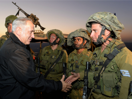 In this handout image provided by the Israeli Government Press Office (GPO), Prime Minister Benjamin Netanyahu (L) shakes hands with soldiers October 15, 2013 in the Israeli-occupied territory of Golan Heights.