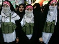 Tehran, IRAN: Iranian women dressed as suicide bombers stand next to a portrait of 19-year-old Palestinian female suicide bomber Hiba Azem Daraghma during a demonstration in downtown Tehran, 31 July 2006.
