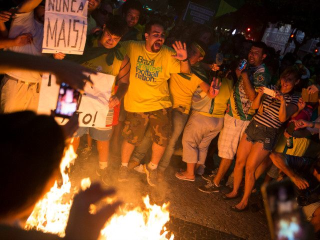 Protesters against Dilma Rousseff, Brazil's president, burn a figure in Rousseff's likeness after watching a televised broadcast of the country's lower house of Congress voting in favor of Rousseff's impeachment at Copacabana Beach in Rio de Janeiro, Brazil, on Sunday, April 17, 2016. Rousseff's presidency is hanging by a thread after Brazil's lower house of Congress voted in favor of her impeachment, a decision that's likely to cheer investors just as it threatens to bring down the curtain on 13 years of leftist rule. Photographer: Nadia Sussman/Bloomberg via Getty Images