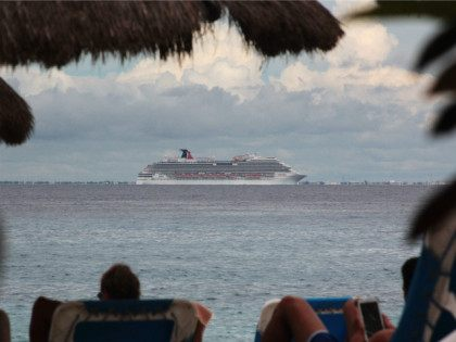 Tourists lie on the beach as cruise ship Carnival Magic is seen near the shores of Cozumel October 17, 2014. REUTERS/STRINGER