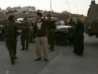 Israeli soldiers speak to a Palestinian man as he waits to cross the Kalandia checkpoint on the main road leading the West Bank city of Ramallah to Jerusalem, 25 November 2007.