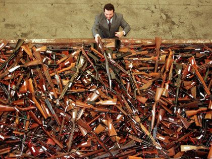 Mick Roelandts, firearms reform project manager for the New South Wales Police, looks at a pile of about 4,500 prohibited firearms in Sydney that have been handed in over the past month under the Australian government's buy-back scheme July 28. REUTERS/DAVID GRAY