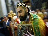 A Coptic priest advances 04 April 2004 inside the Holy Sepulchre Church in Jerusalem on Palm Sunday as hundreds of followers of the different branches of Christianity began Easter celebrations by parading through Jerusalem's Old City before praying at the Church of the Holy Sepulchre, believed to be the final …