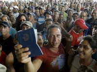A Cuban migrant man receives his passport with the visa granted by the immigration office at the border post with Panama in Paso Canoas, Costa Rica November 14, 2015. REUTERS/JUAN CARLOS ULATE left1 of 3right left2 of 3right left3 of 3right left1 of 3right