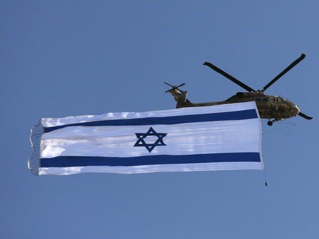 An Israeli Blackhawk helicopter performs with the Israeli flag during an air show as part of a graduation ceremony of Israeli pilots at the Hatzerim air force base in the southern Negev desert, near the city of Beersheva, on June 25, 2015.